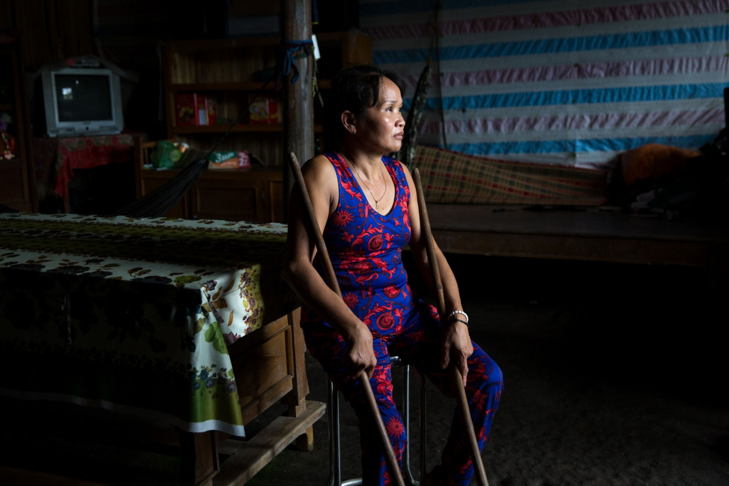 Ex-rice farmer Nguyen Tuyet Khanh sits in the main room of her house. She has been physically disabled since she was 3 years old which has made life as a farmer exceedingly difficult. Life was also made harder due to an increased salinity of her land which led to the rice crops failing. As a result, she switched to a type of water reed that grows well in brackish water and which can be dried and woven in to mats for extra income. At present, she is able to weave two mats a day and makes around US$1 profit per day from selling them. But even now the reed is becoming more fragile due to too much rain and she is unable to harvest the reed in the rainy season anymore.