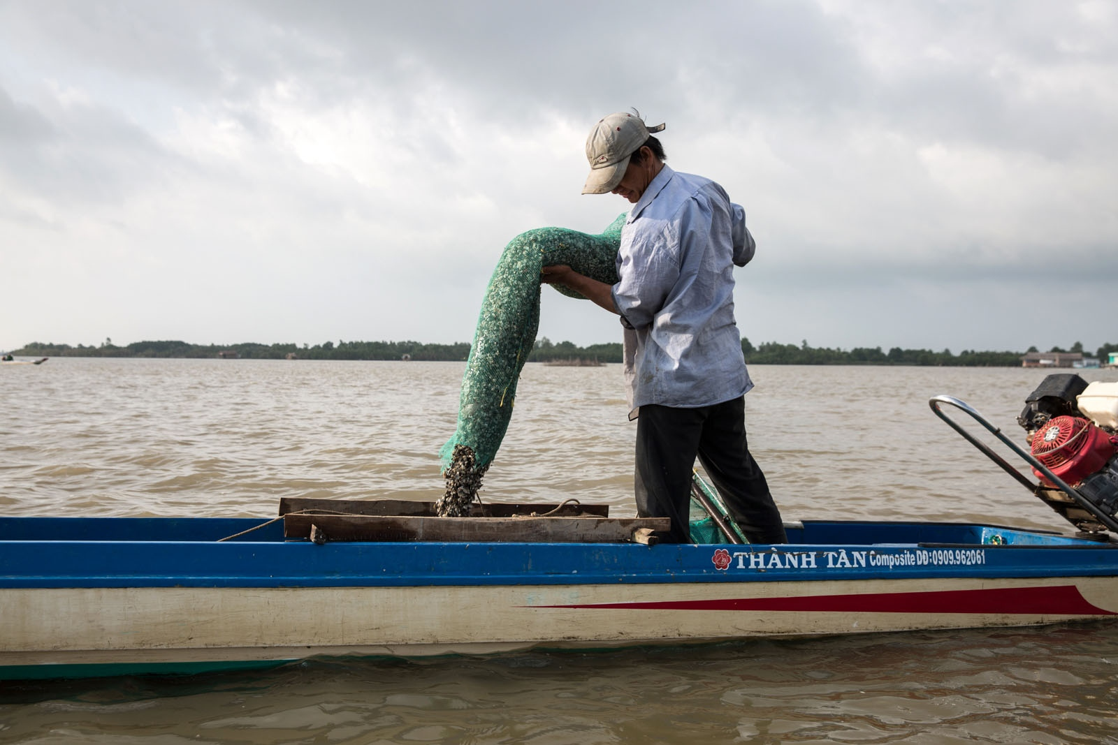 Local fisherman Le Van Mua, 35, collects small snails from his nets at dawn on Thi Tuong Lagoon. He is very careful only to collect the small snails, the bigger ones he put back in the water to breed again. He then sells the snails to crab farms to feed their crabs and is able to make around US$10-US$15 profit per day. But he has only been doing this for a year after realising there was a demand for it and with fish stocks reduced so much it seemed a good alternative to fishing.