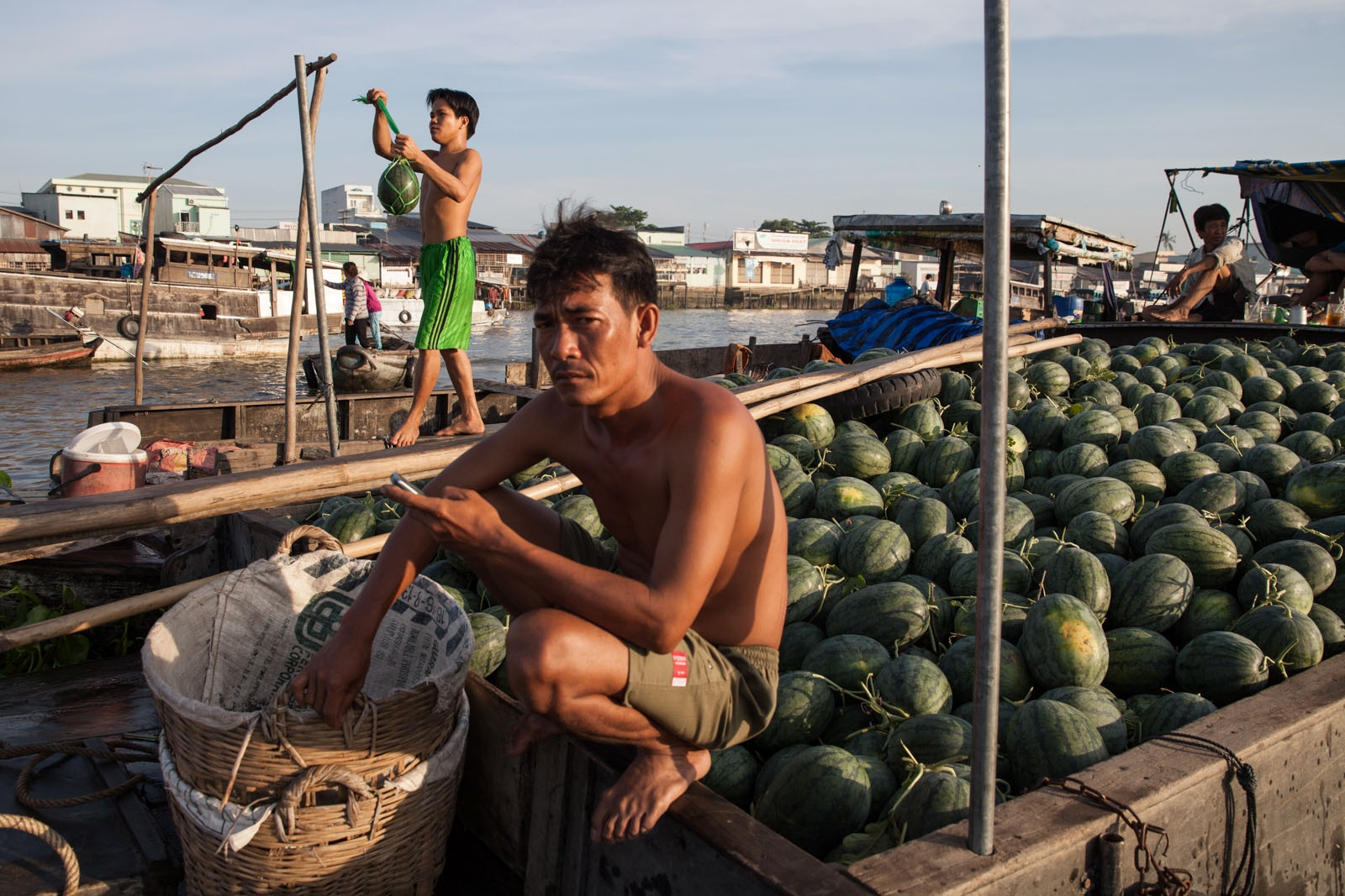 At Cai Rang floating market a man ties a watermelon to a pole advertising what his families boat is selling.