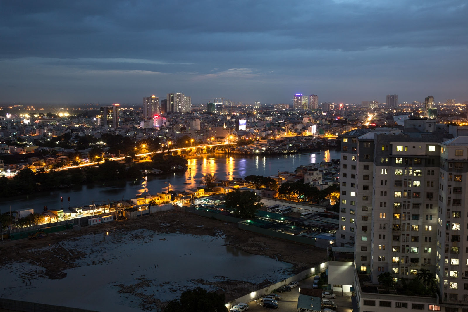 A view of Ho Chi Minh at dusk showing the rapid urbanisation of the city. In the foreground lies a water-logged construction site that will soon become a condominium. It is Vietnam's most populated city of approximately 12 million people, sitting at an altitude of little over 10 meters above sea level and is surrounded by rivers. With climate change causing sea levels to rise Ho Chi Minh and the Delta to its Southwest could be at serious risk in the future.