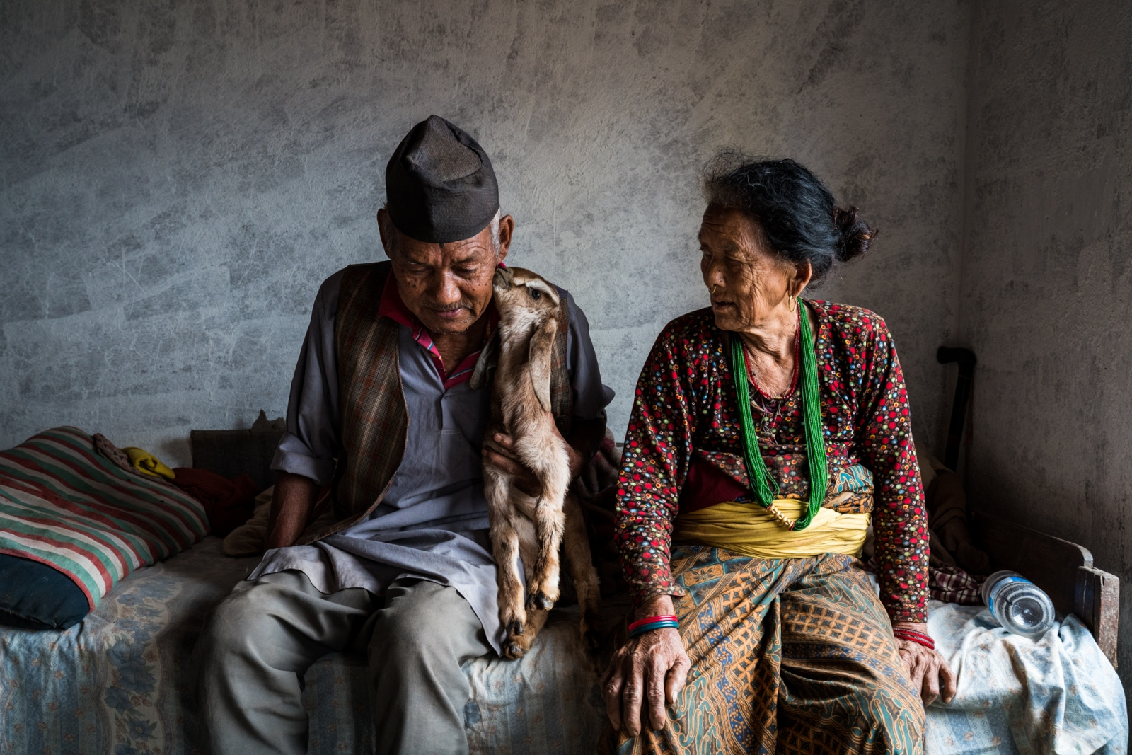 Babulal Tamang, 82 and Myrani Tamang, 79 sit with their baby goat inside their home. Thurloparsel, Nepal.