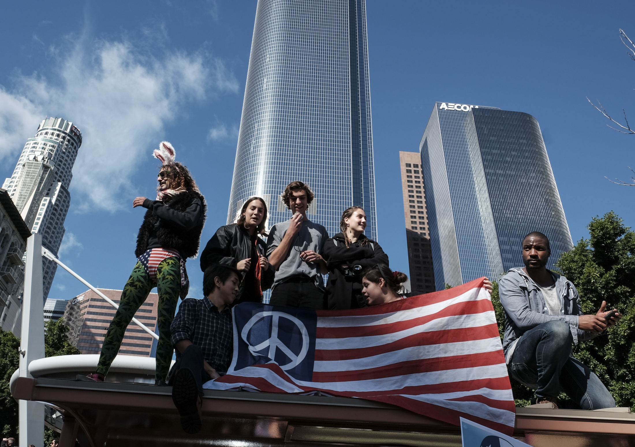 Participants sit on top of a bus stop during the Women's March on January 21, 2017 in Los Angeles, California. Tens of thousands of people took to the streets of Downtown Los Angeles for the Women's March in protest after the inauguration of President Donald Trump. Women's Marches are being held in cities around the world.
