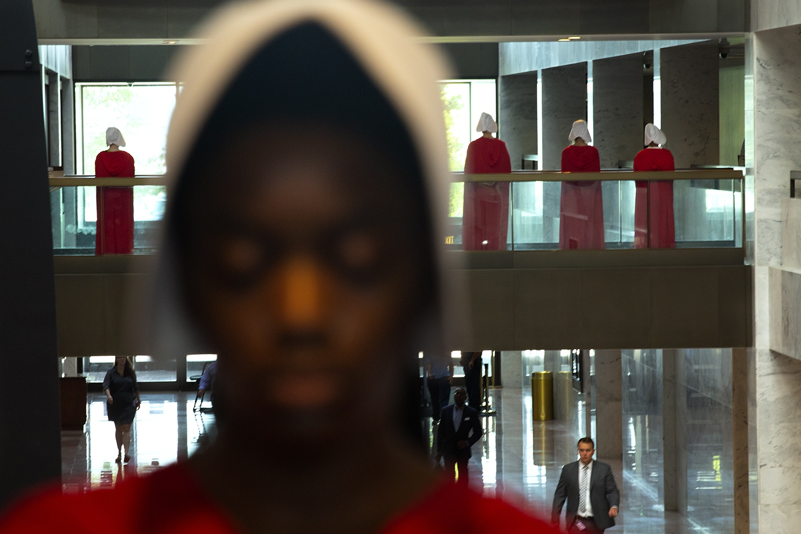 Women dressed as characters from A Handmaid's Tale stand quietly in the Hart Senate Office Building on September 5, 2018. They are associated with Demand Justice and are protesting Brett Kavanaugh's nomination to the U.S. Supreme Court.