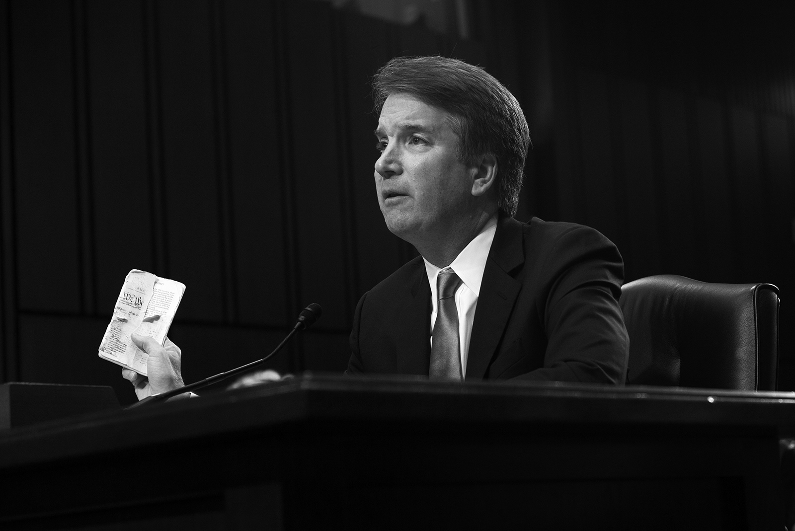 Brett Kavanaugh holds a copy of the U.S. Constitution during his confirmation hearing.