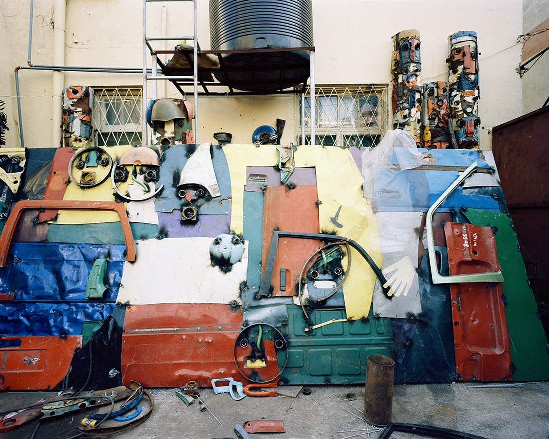 Gonçalo Mabunda working at his studio in Maputo, Mozambique. July 2016. This image was made with color film with a Mamyia 7II camera, in 6x7 format. It was scanned by the artist with Hasselblad flextight X1 professional scanner.  This has a edition of 6 + 3 PA  in the size 75x94 cm. It is printed by the artists in archival quality.