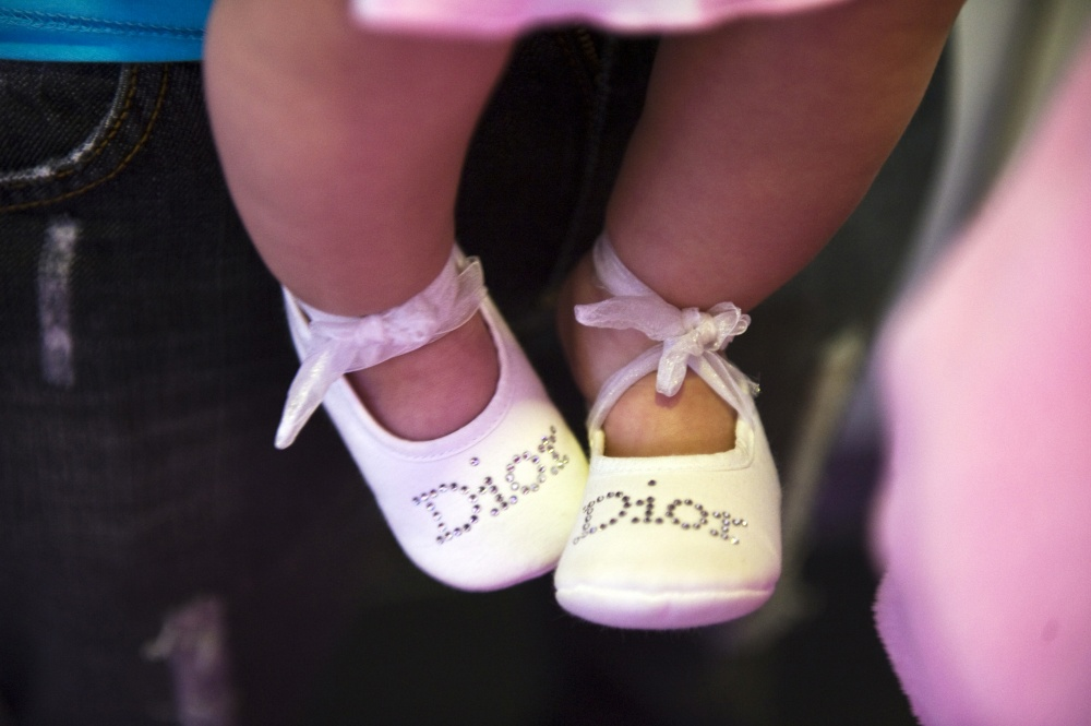A baby wears designer Christian Dior shoes at a 9-year-old's beauty birthday party held at Frizzy's Chez Lulu Beauty Salon in Beirut, Lebanon.