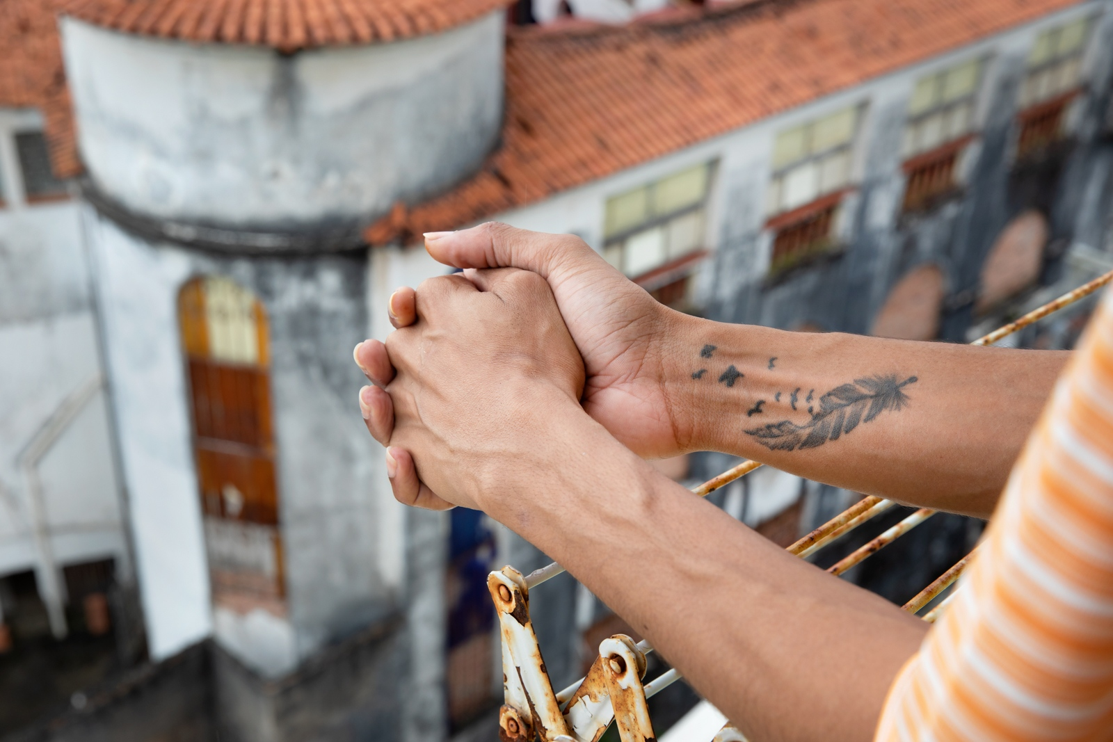 """Teodoro, 28, stands at the window. His tattoo symbolise the """"penas"""" (feathers, also mean sorrows in Portuguese) transforming in free birds in the sky. Homosexual Cis, Drag Queen of Coletivo Monstras, Teodoro was a student at Architecture school and left to try his chance at the Theater Course in University of Bahia. Salvador, Bahia."""