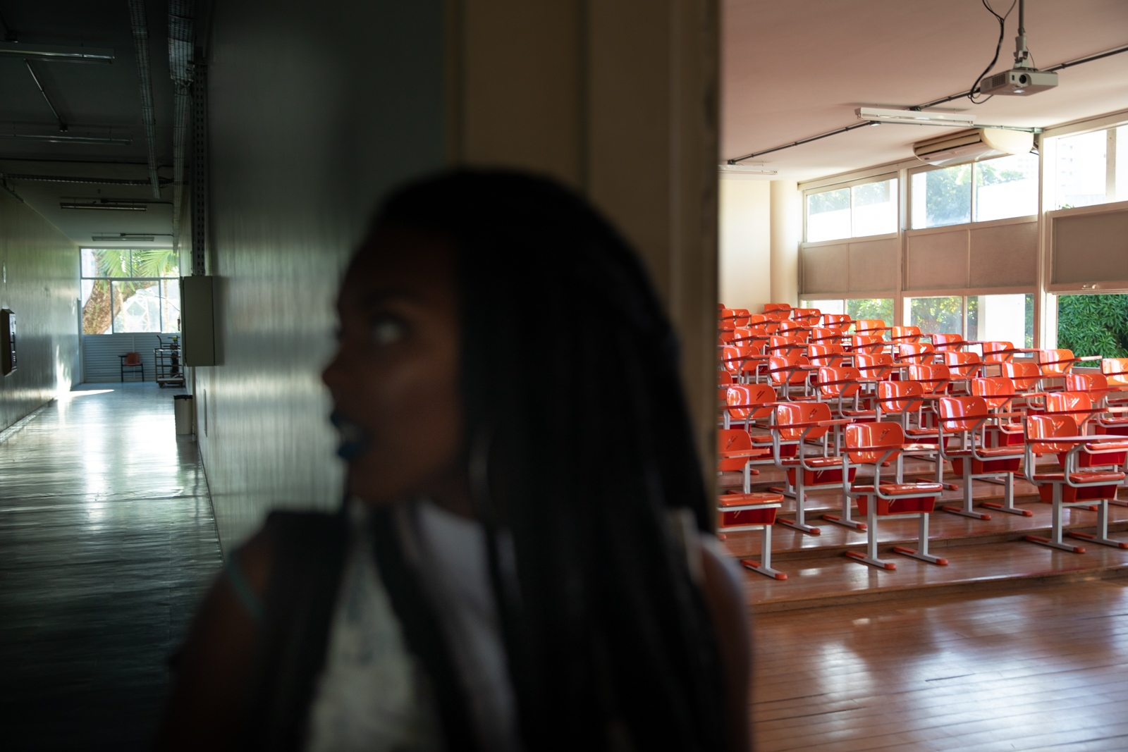 Samira Soares, 23, student at Humanities course, stands at the door of a university empty room of the University of Bahia. Born and raised in the countryside of Bahia, daughter of a housekeeper, Samira came to Salvador to try a better chance then her mother, trying to scape the housekeeper faith of so many young Black Women of Brazil.  Without money to studies and bills to live in Salvador, Samira entered University with the help of some student grants of the old Government and thank to this financial support she was able to pay her life and keep her University studies.  Since 3 years ago and today, almost all of the student grants and programs to help young Brazilians to study are being closed and failing to disappear. Thousands of young, many from Afro-Descendances, are losing their opportunity to construct a better life.   Salvador, Bahia.