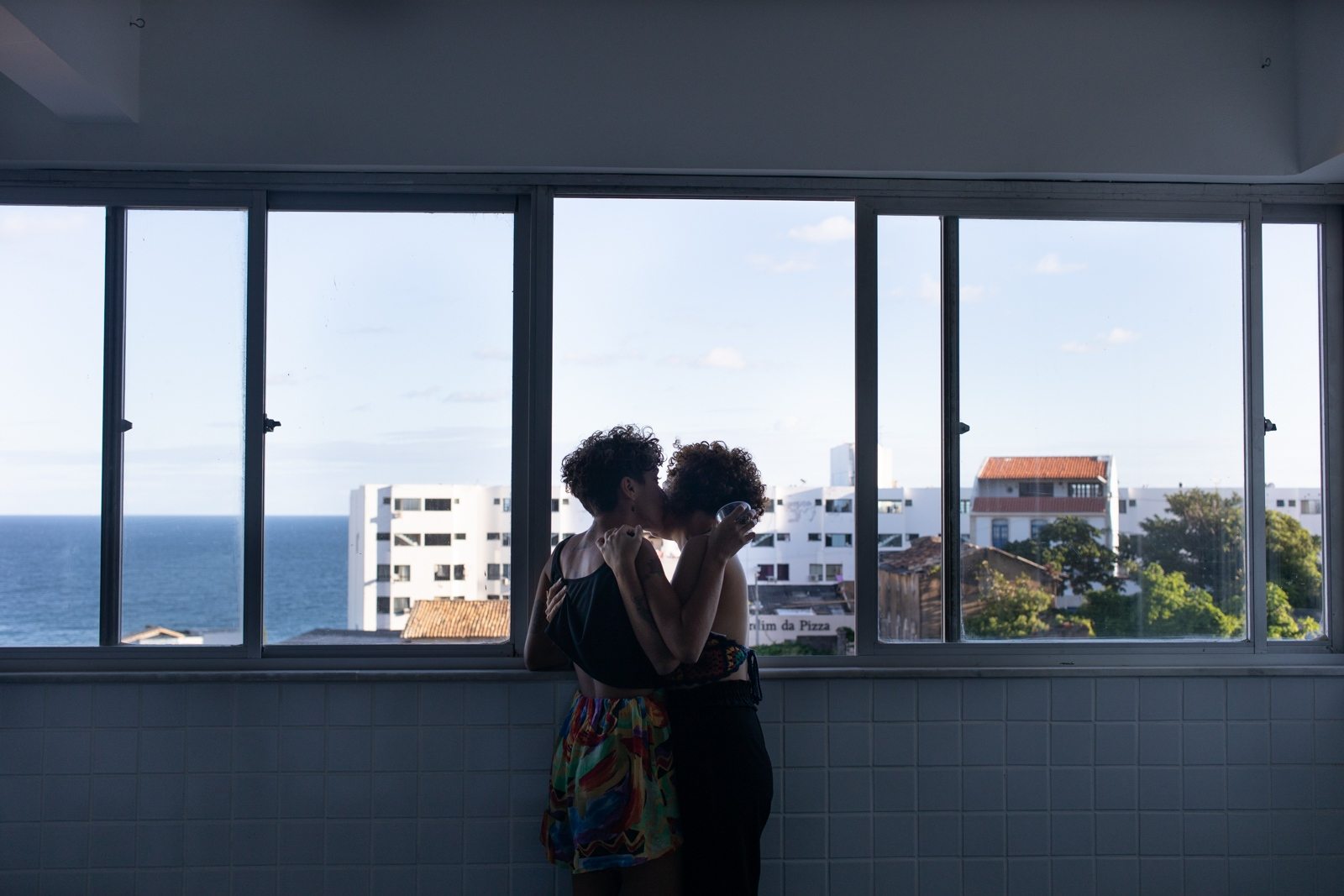 Jessica Magliano, 26 and her girlfriend Luana, kissing at the window of the social floor of the building in Salvador. They are now living in Salvador to study, coming from Joao Pessoa, Alagoas, where both frequents parties and gatherings from Tombamento generation. Both find Salvador a better city to live - in regards with studies. As a lesbian couple, they think the actual times are a hard moment to express themselves freely  as the radical  right wing is growing strongly in the country, they feel not entirely safe. Salvador.