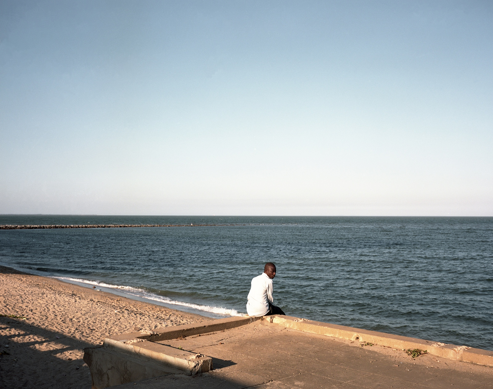A local man set in front of the Indian Ocean near the seaside road of Maputo, part of the Ring Road Project. The project costs was US$ 315 million and it has still to be paid by the State.