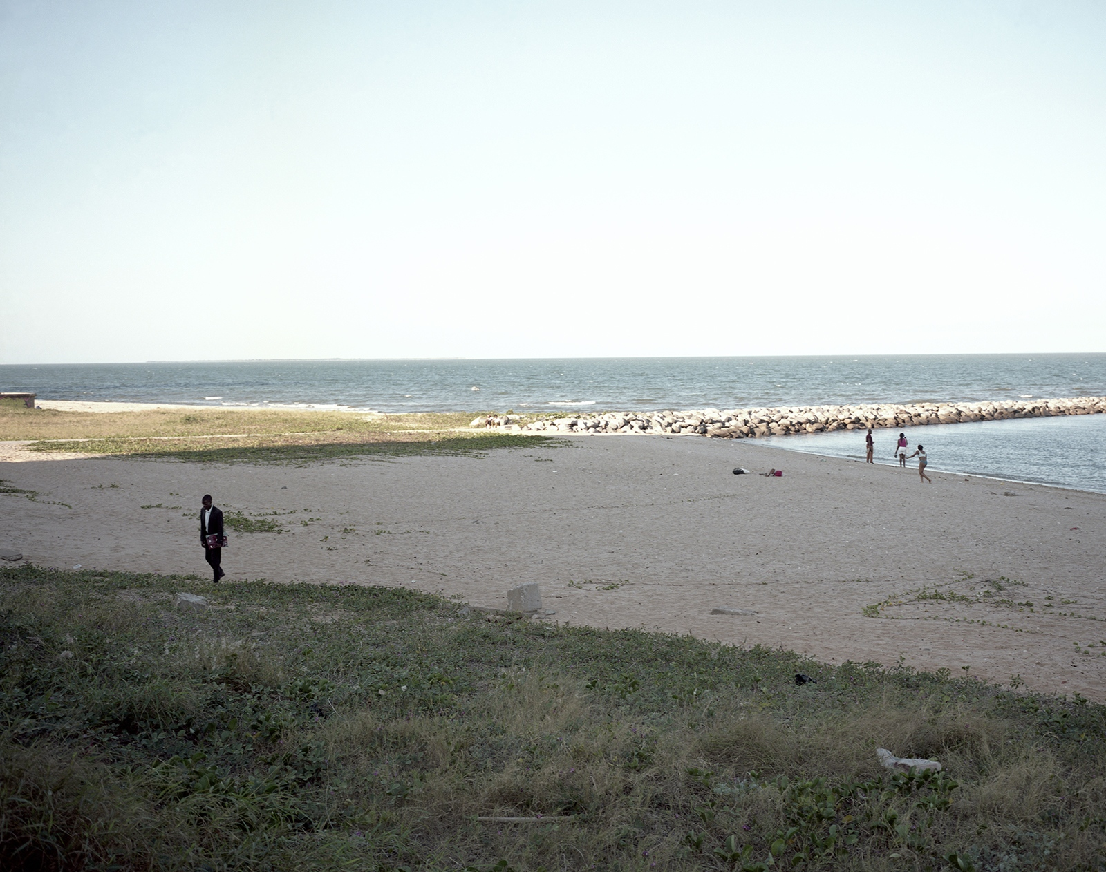 Daily-life on the beach close to the seaside road of Maputo. The project cost was US$ 315 millions and it has still to be paid by the State, also the high speed road and the absence of bridges to cross the road increase the number of car accidents involving pedestrians.