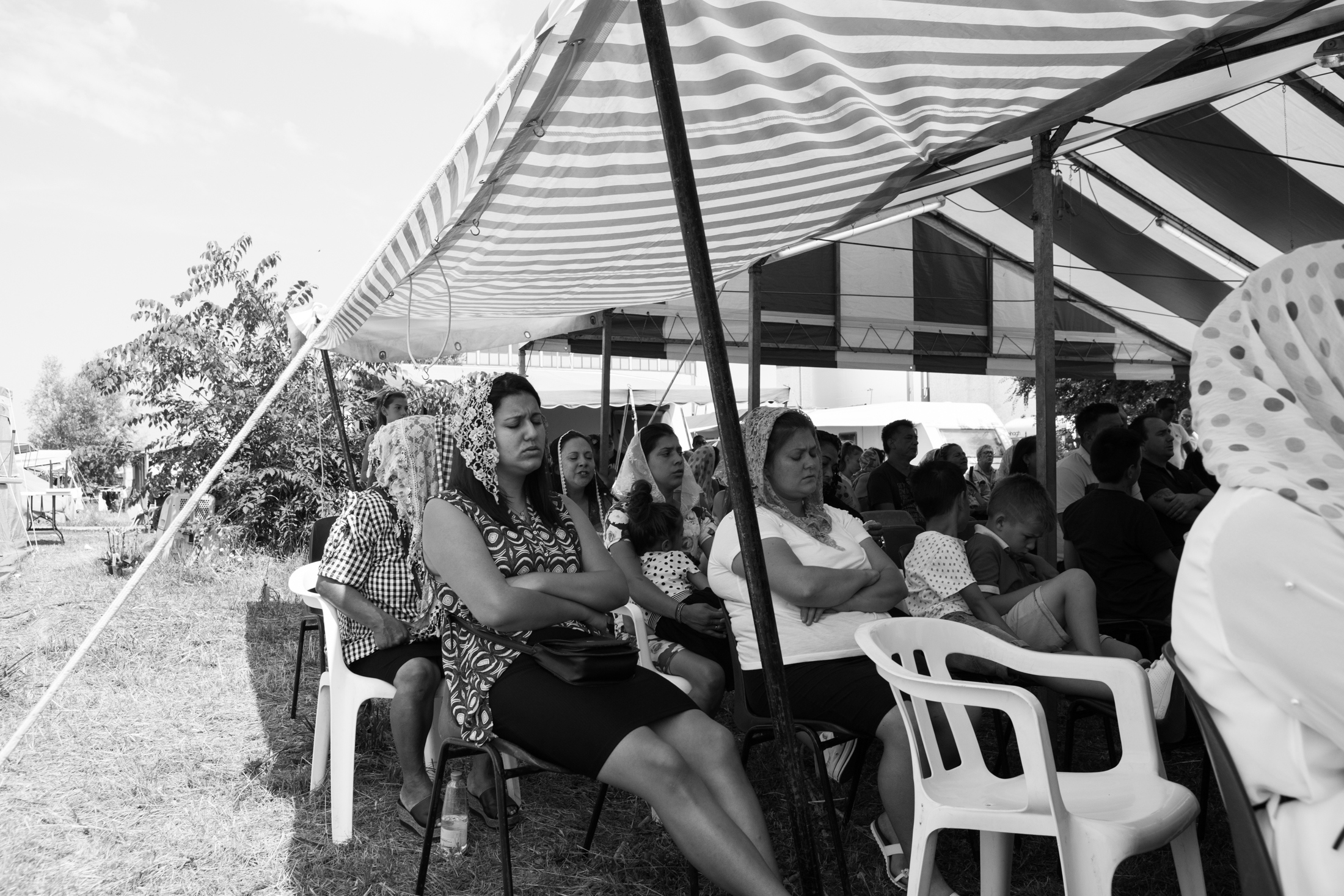 June 2018, Nomad camp near to Castelnuovo Rangone, Emilia-Romagna, Italy. The faithful of the Sinti community pray during the evangelical worship. The evangelical religion is becoming more and more established within the community, thanks to the possibility of redeeming oneself from sins and of embarking on a new way of life. In fact, these cults are reaching ever greater numbers of believers through adult group baptisms and children.