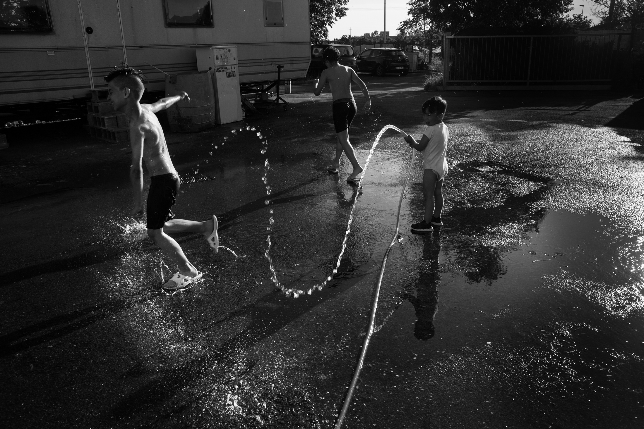 May 2017, nomad camp of Castelnuovo Rangone, Emilia Romagna, Italy. A group of children plays with the water cane, to counter the torrid heat that has characterized the Po Valley since the spring. Within their area of the field there is only one tree, and in the absence of shade the temperature and the heat are perceived much more intensely, also due to the asphalt on which the field itself rises.