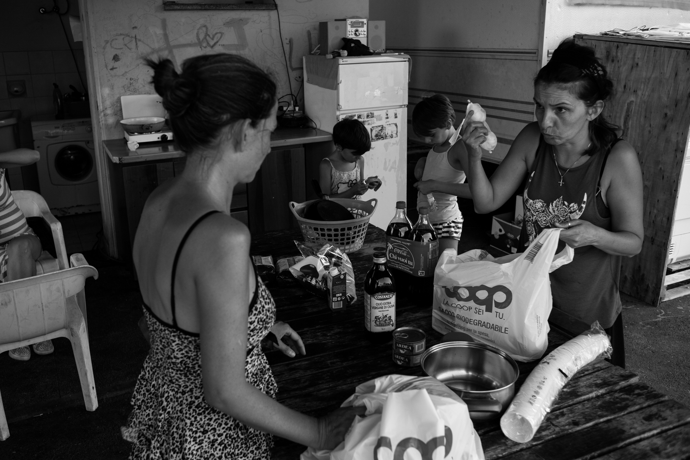August 2017, nomad camp of Castelnuovo Rangone, Emilia-Romagna, Italy. Lady and sister Simonetta arrange the shopping and prepare to cook lunch for both families.