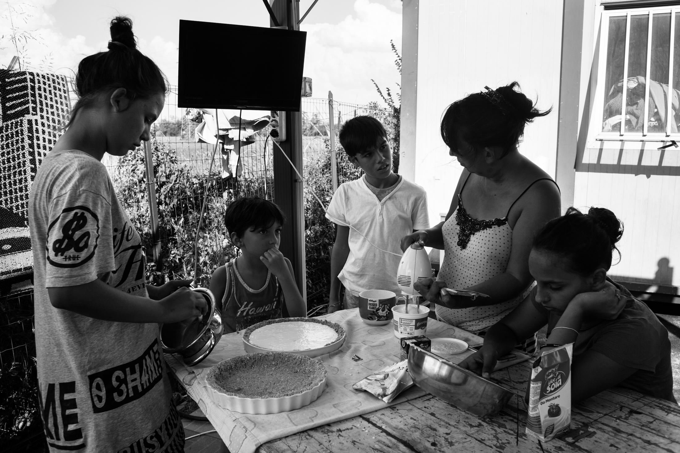 August 2017, nomad camp of Castelnuovo Rangone, Emilia Romagna, Italy. Linda prepares two cakes with the help of Vicki, her daughter and her grandchildren, in front of her mobile home. She will bring the cakes to a nomad camp not too far away, where she has been invited to dinner by some of her relatives.