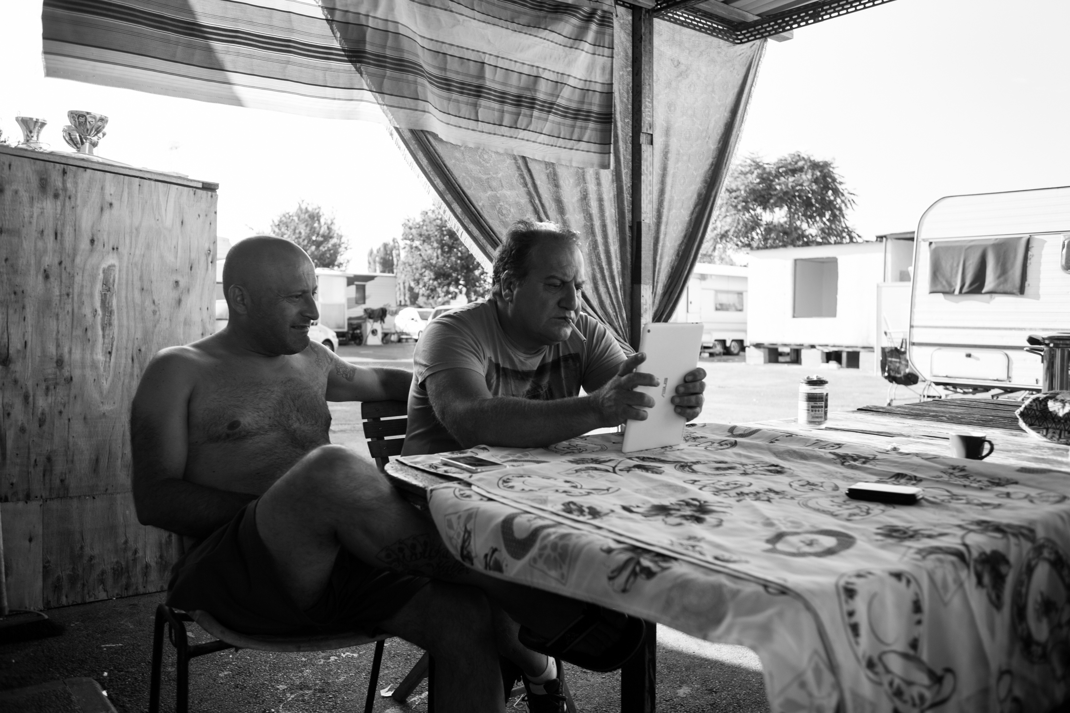 August 2017, nomad camp of Castelnuovo Rangone, Emilia-Romagna, Italy. Two adults in the community watch some videos from the tablet.
