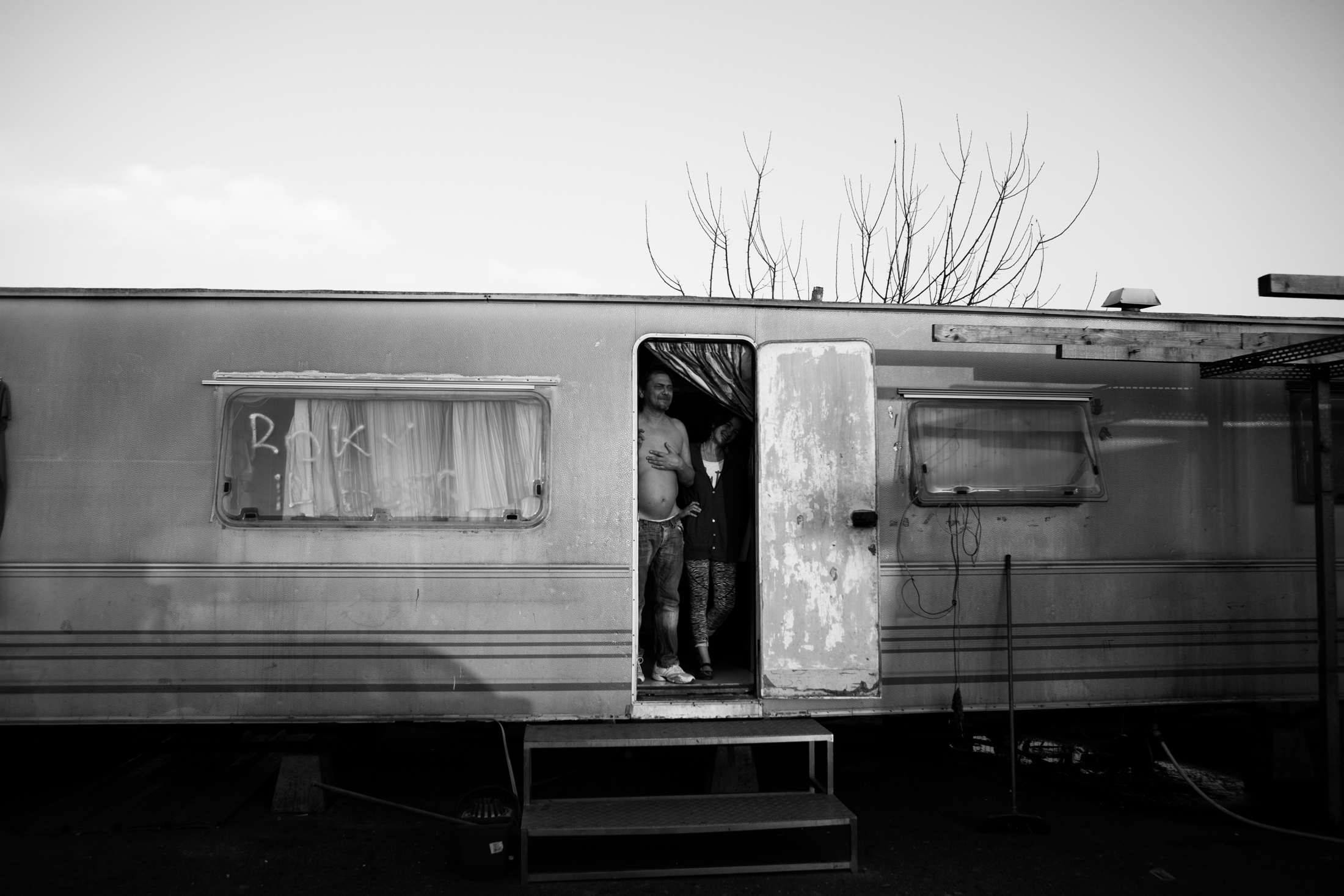 March 2017, nomad camp of Castelnuovo Rangone, Emilia Romagna, Italy. Rocky and his wife greet friends from the threshold of their mobile home.
