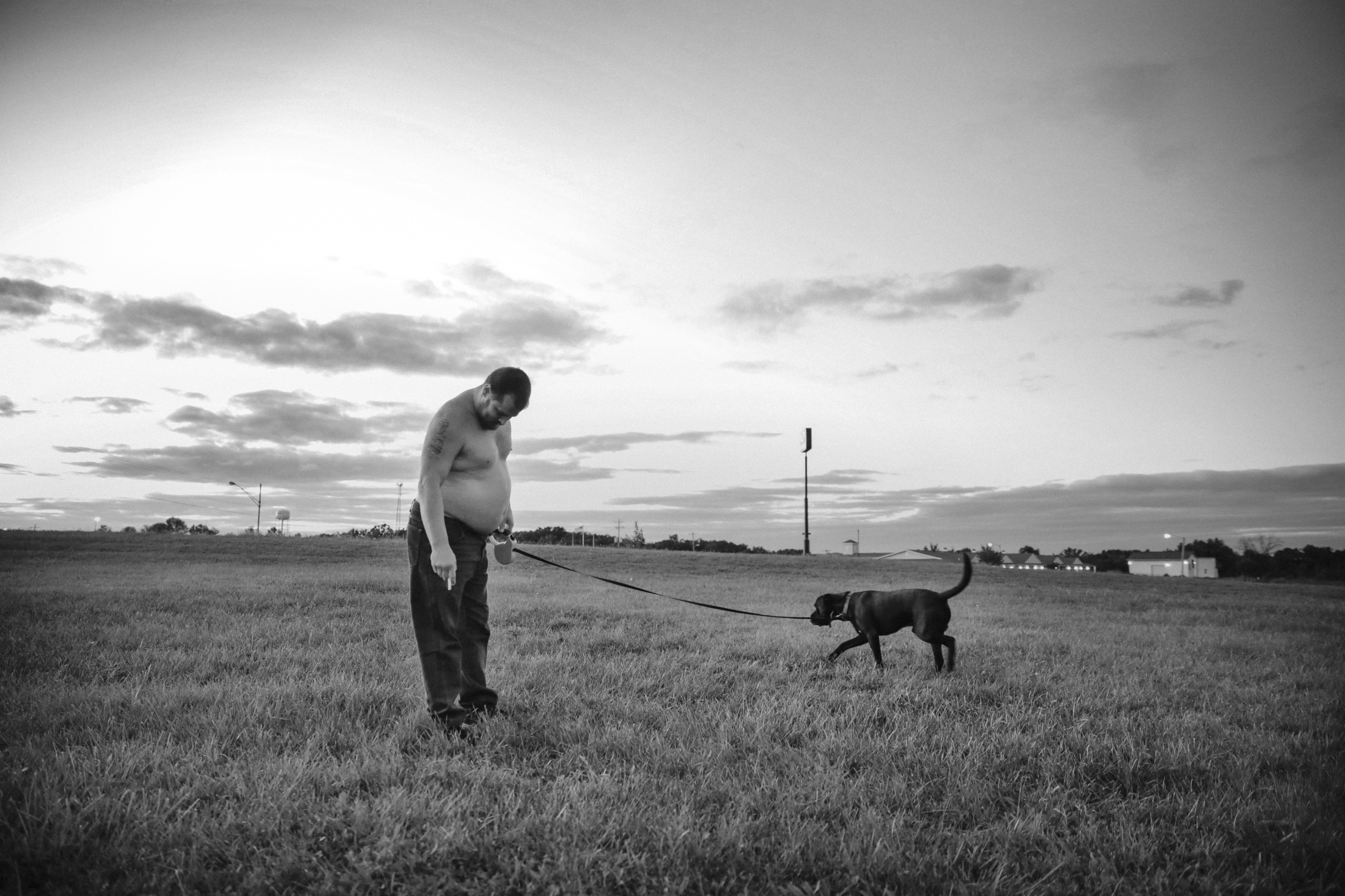 Anthony Young walks his 7-year-old black lab-pei dog, Sampson, near Chateau Inn & Suites in Cuba, Missouri. Since July, Young, his fiancé Dawn Klages, her father Ty Klages and Sampson have been living together in a two-bed motel room after losing the house where they had lived for the past five years.