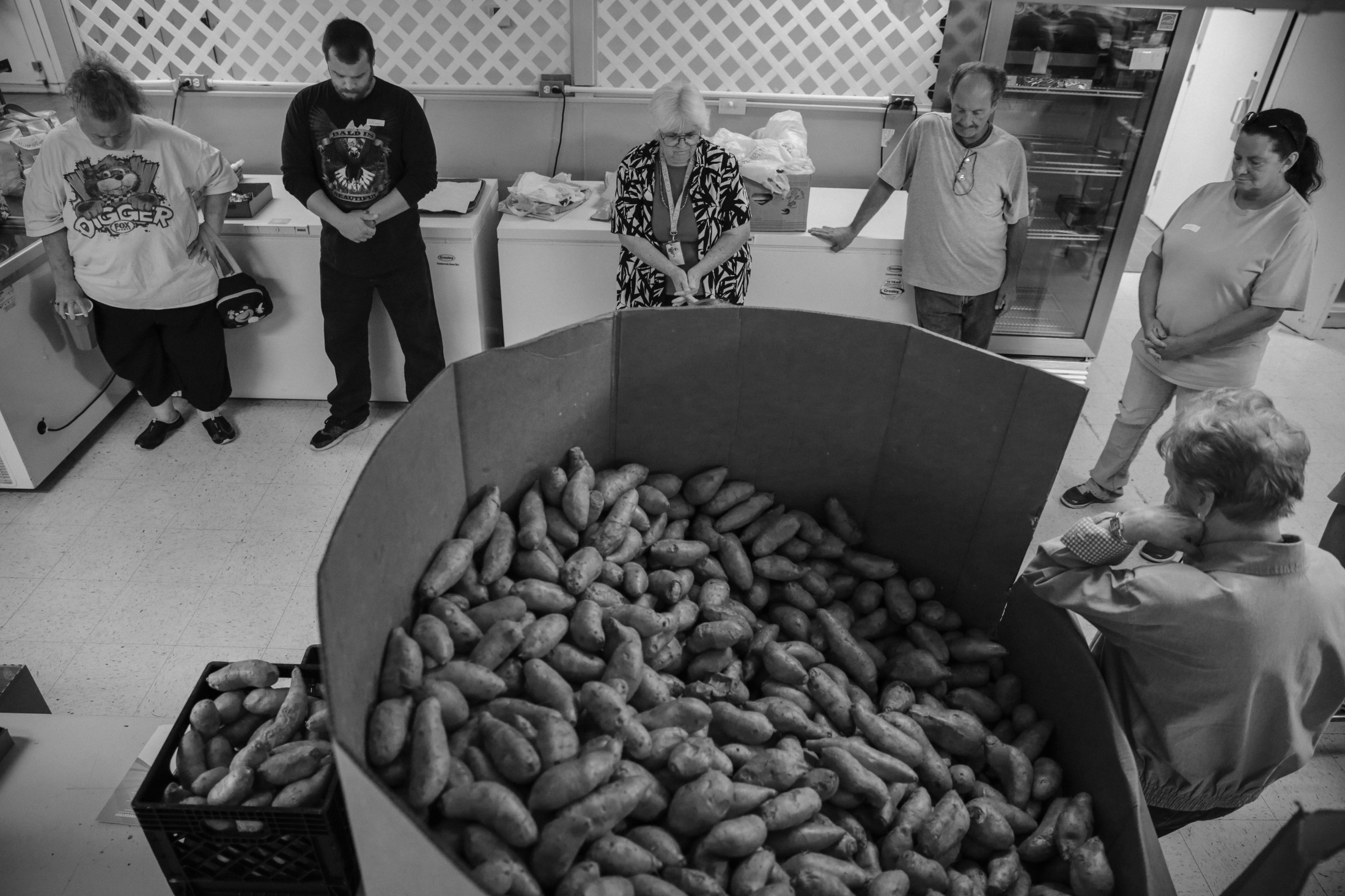 Volunteers listen as Barbara Jopling, the director of Cuba Ministerial Food Pantry, prays near a stack of sweet potatoes to start the day. About a year ago, Anthony was charged with possessing a sawed-off shotgun and has volunteered at the pantry to fulfill his community service hours.