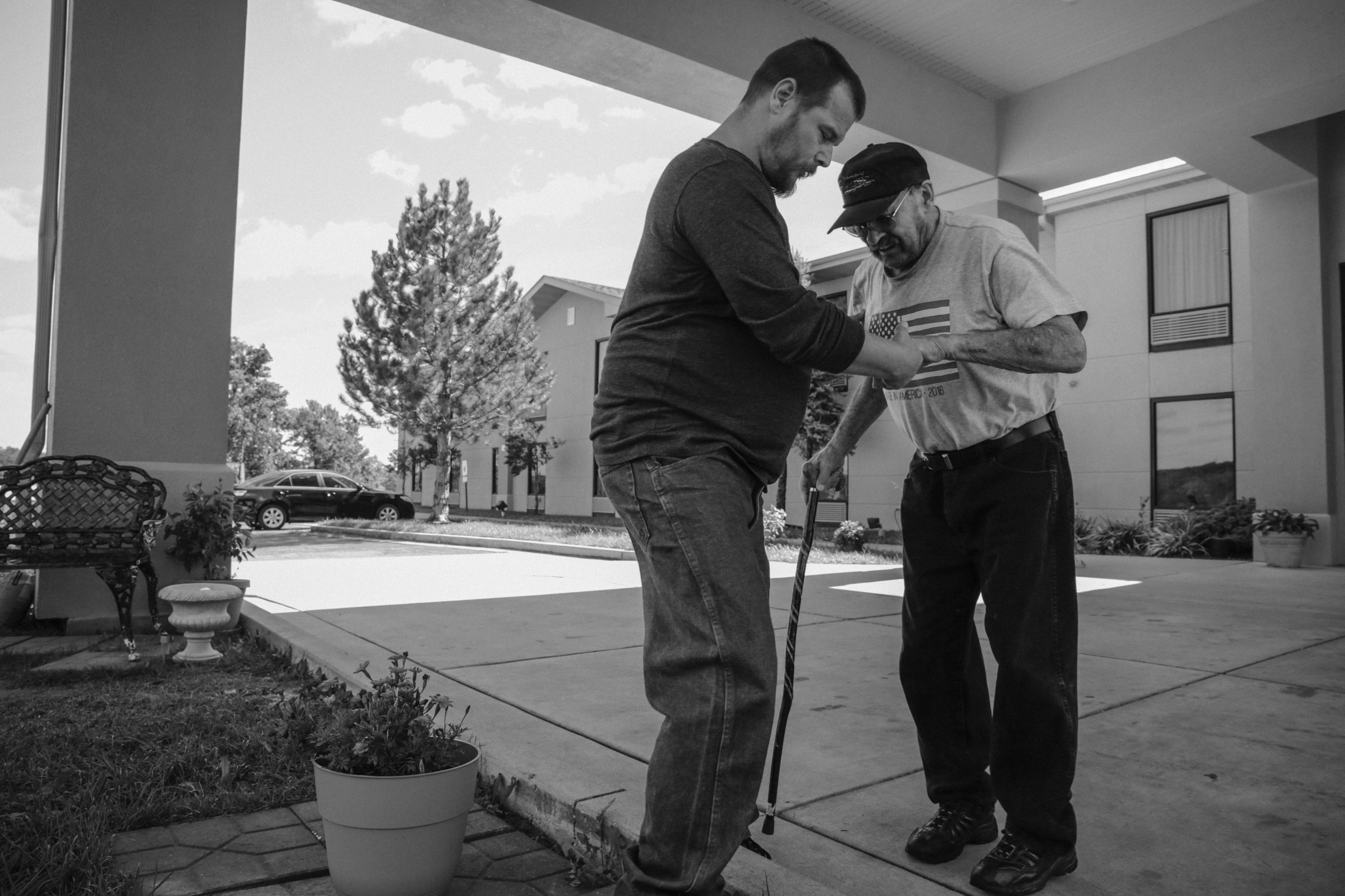 Anthony assists Ty while taking a walk together outside their motel room. Six months ago, Anthony stopped using meth after two decades to become a responsible person. Since then, he has spent most of his days caring for the family.