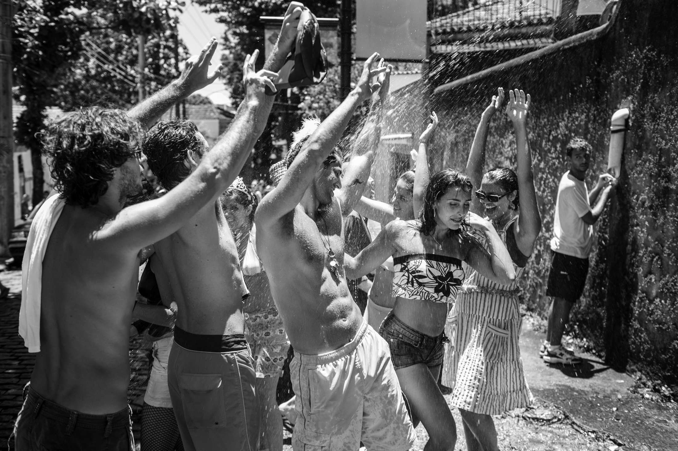 A group of young men and women has fun while water is being sprayed on them from a house during Céu na Terra carnival street party in Santa Teresa. February 2007.