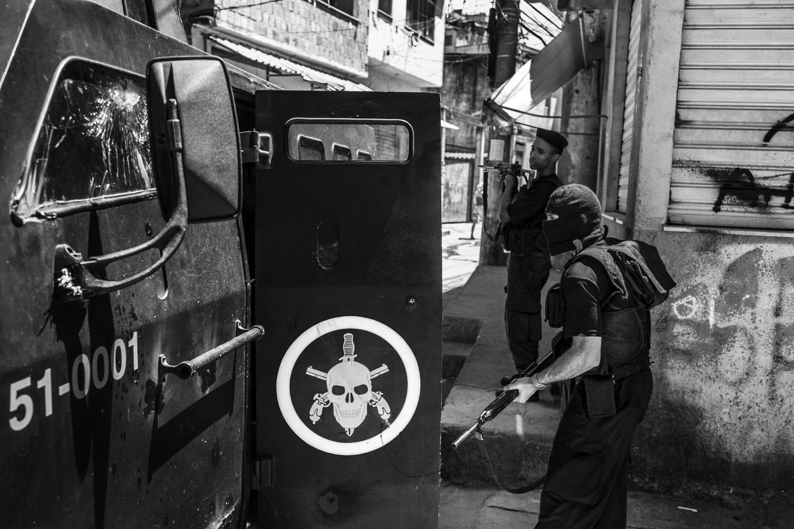 "Soldiers from the BOPE (Special operations unit from the Military Police) enter their armored car known as ""Caveirão"" during a police operation against drug traffickers of the Red Command gang in Complexo do Alemão favela complex. March 2007."