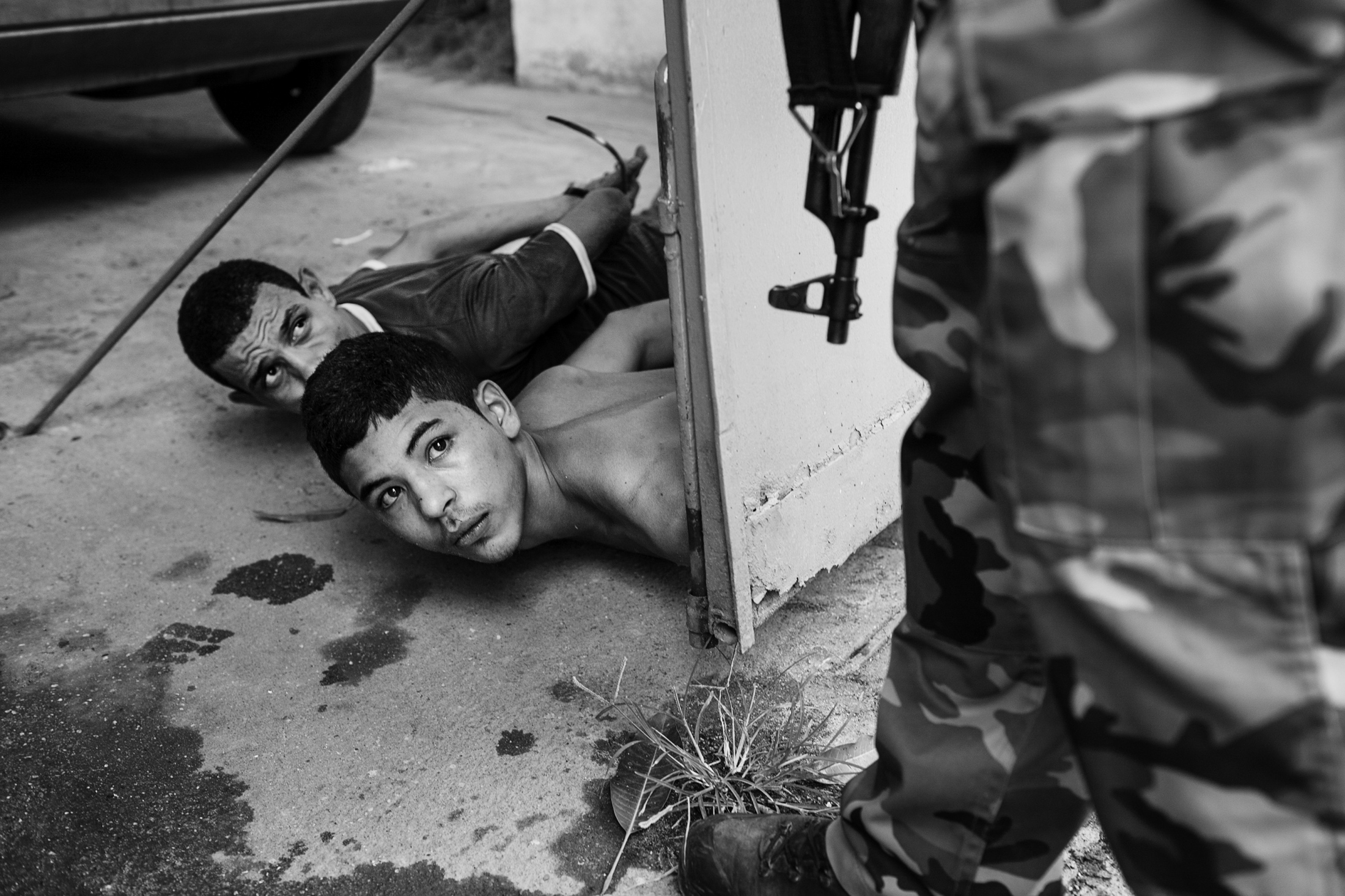 """Two suspected members of the drug trafficking gang, """"Terceiro Comando"""" (the boy in the center of the image is 15 years old) are arrested during a police operation in the Acari favela in northern Rio de Janeiro. February 2008."""