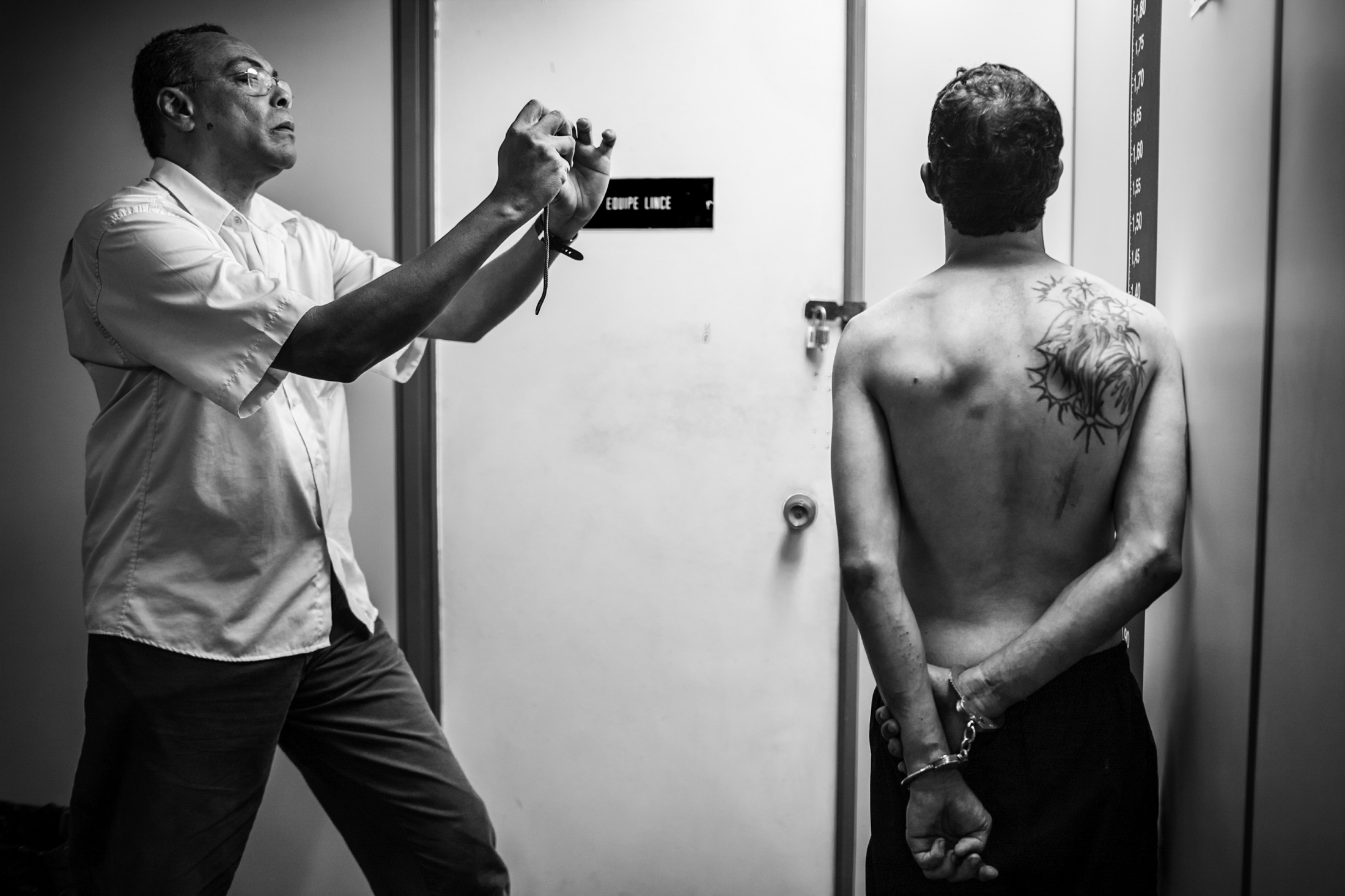A policeman from DRAE photographs the mug shots of João Paulo da Costa, detained as a suspected drug dealer. He will await trial in detention. February 2008.