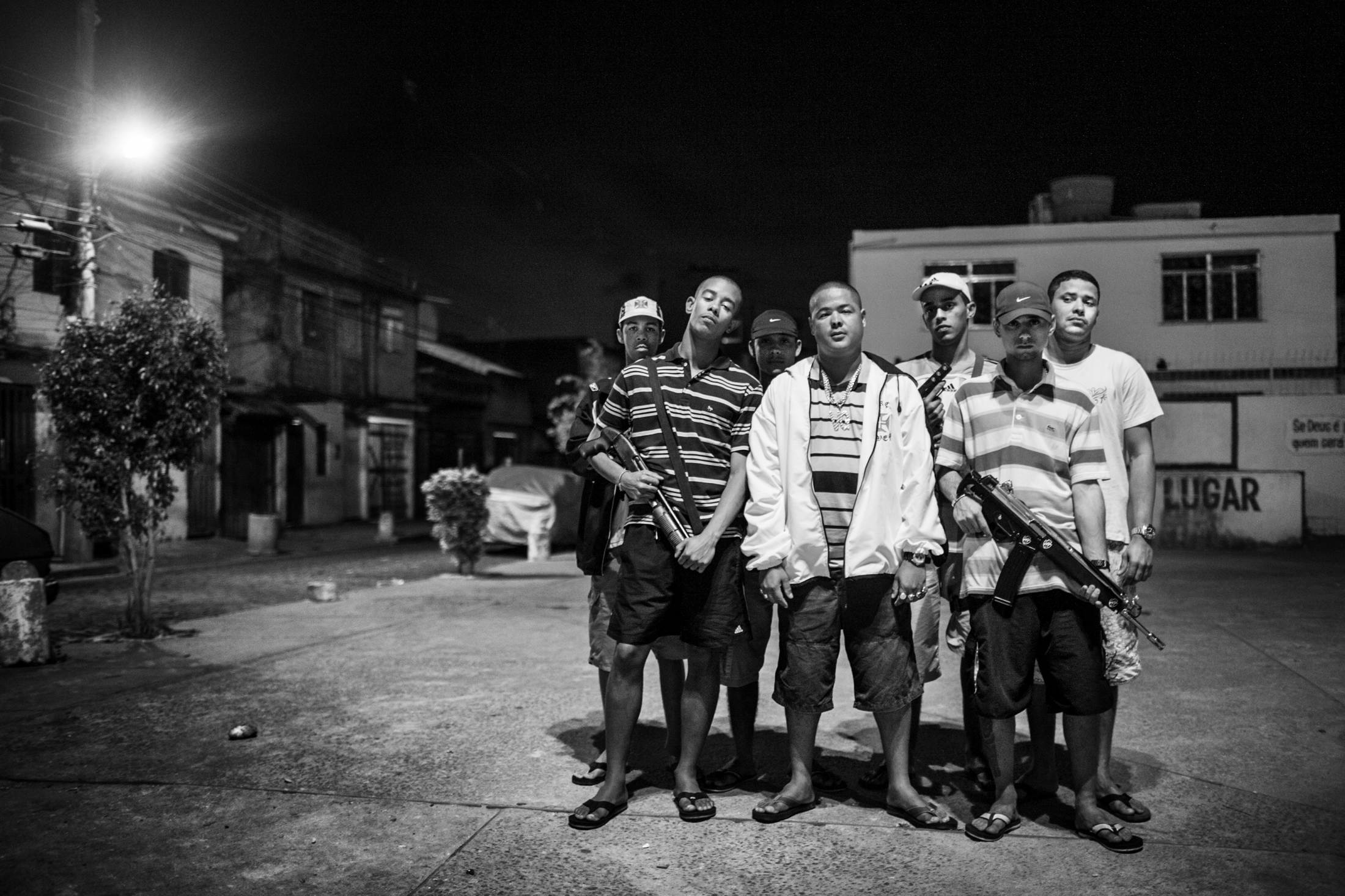 """Young people who belong to the """"Third Command"""" gang pose for a group portrait inside the Parque Royal favela on Governor's island in northern Rio de Janeiro. The man in the middle in a white coat is """"Vesguinho"""" the leader of the group. He was later killed by the military police in June 2009. July 2008."""