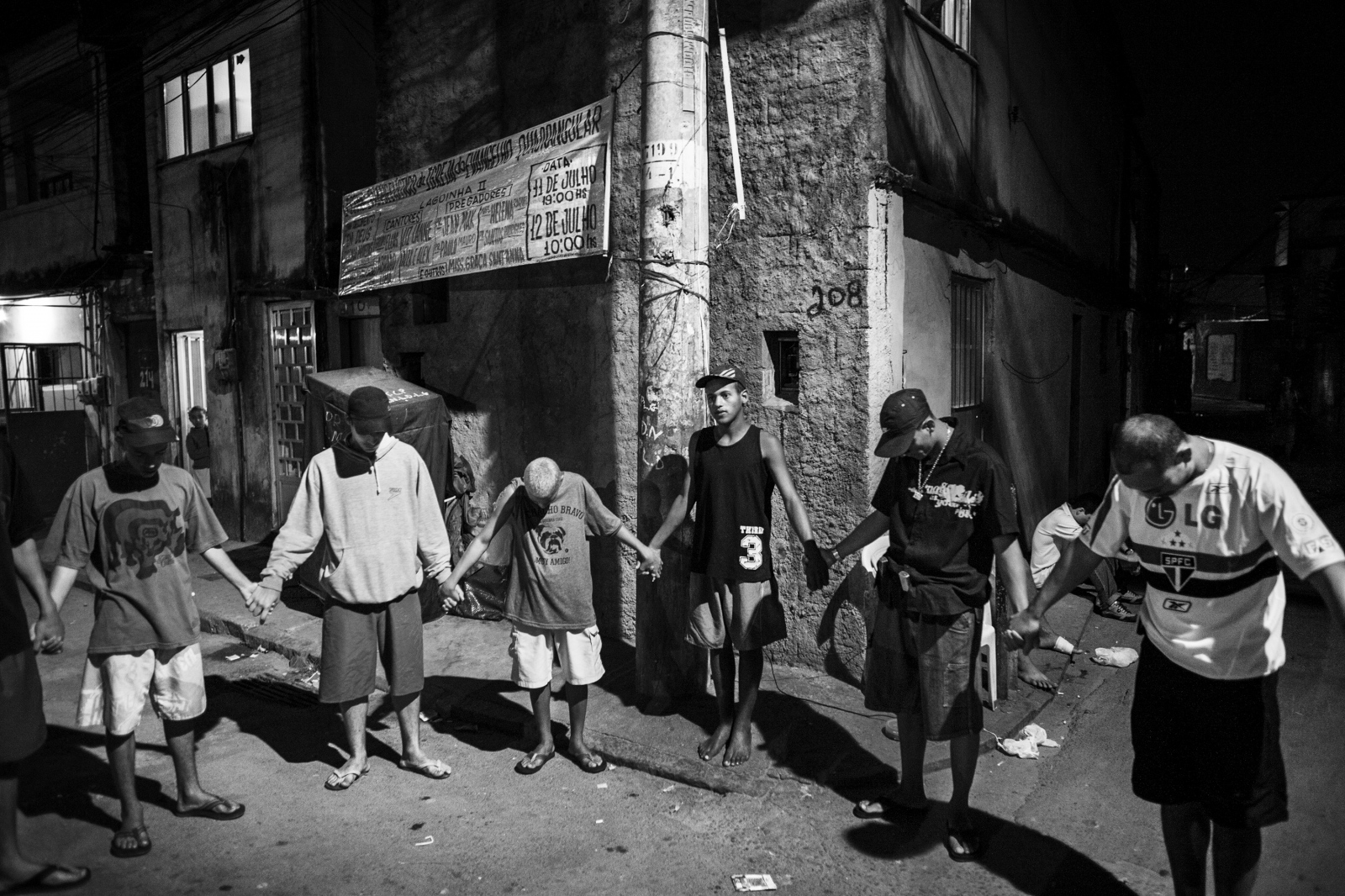 Young men involved with drug trafficking take a break from their shifts to pray when an evangelical preacher visits the Praia da Rosa favela on Governor's island, northern Rio de Janeiro. July 2008.