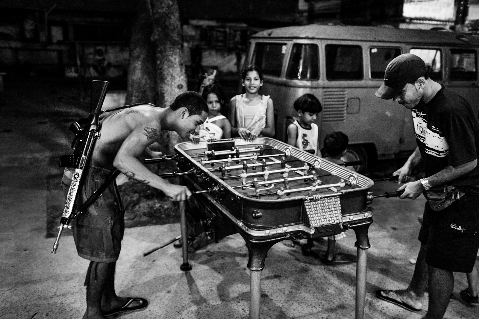 "A young man, known as ""Novinho"" and involved with drug trafficking, plays foosball with an assault rifle on his back in Morro do Dendê, a favela where an estimated 50.000 people live in northern Rio de Janeiro. July 2008."