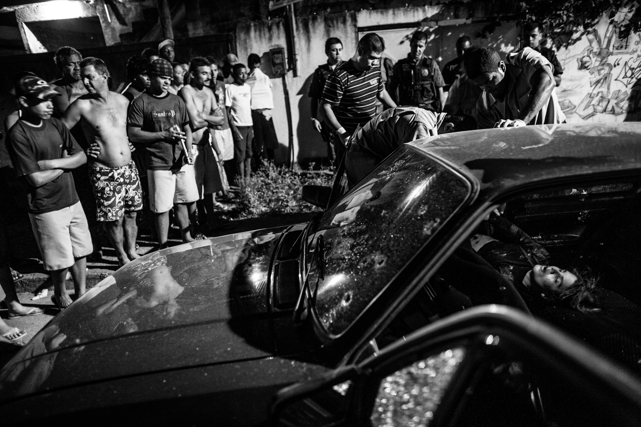 A woman's body is removed by firefighters from a crime scene where three people were shot dead inside a car in Santa Cruz, on the outskirts of Rio de Janeiro. July 2008.