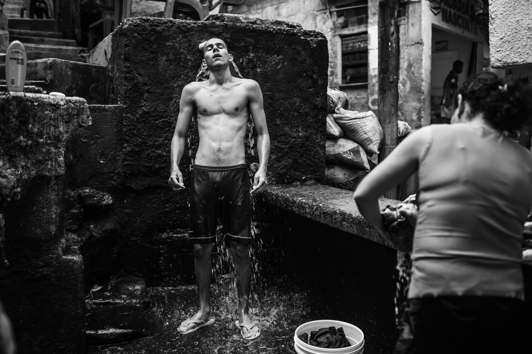 A young man takes a shower in a public water fountain in the Dona Marta favela. A problem with the water pumps left half of the favela with no water for several days. April 2009.