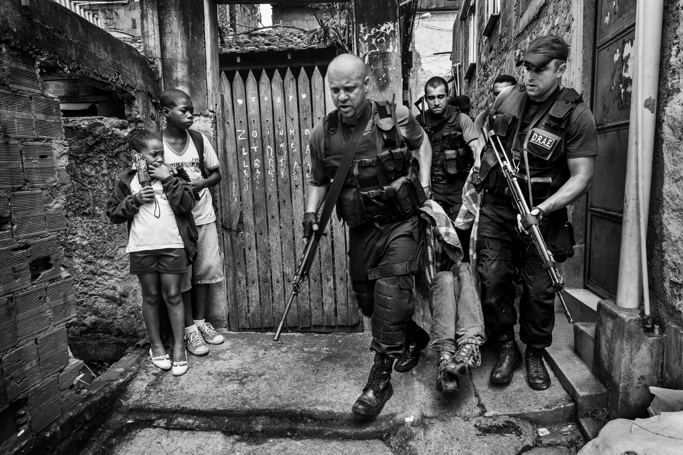 """Policemen from DRAE (Civilian Police division against weapons and explosives in Portuguese) carry the body of a young man, while two children coming back from school look at the scene. This is a case of """"resistance to authority."""" After allegedly being told to stop by the police, the suspect """"resisted"""" and was shot and taken to the hospital. In 2009 alone, the police officially killed 1049 people with this practice. November 2009."""