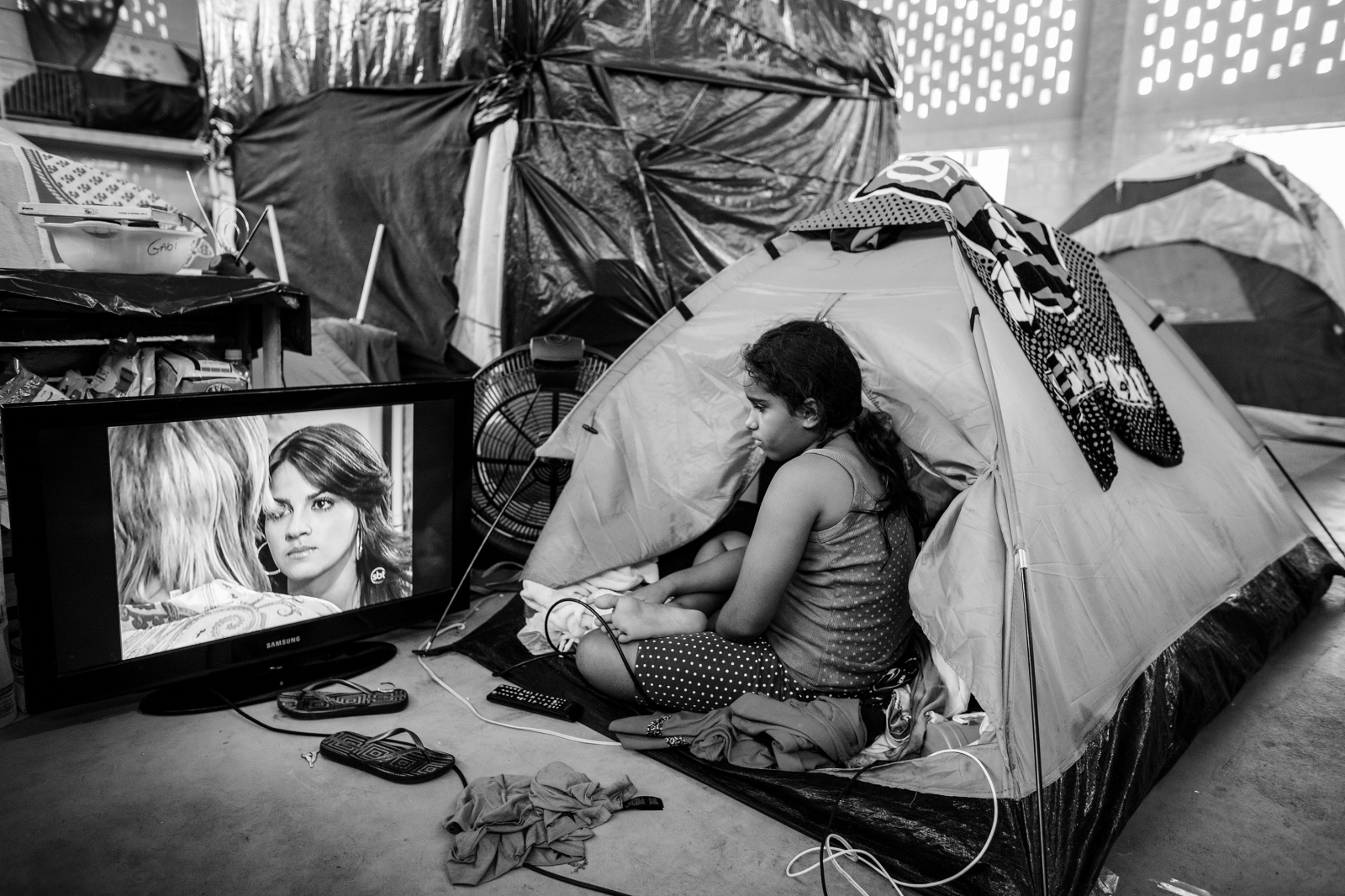 A young girl living in a tent, inside of a catholic church on Governor's island watches a telenovela on TV. A group of squatters that occupied an abandoned factory were evicted and the church offered temporary shelter where they could live in tents. June 2014.