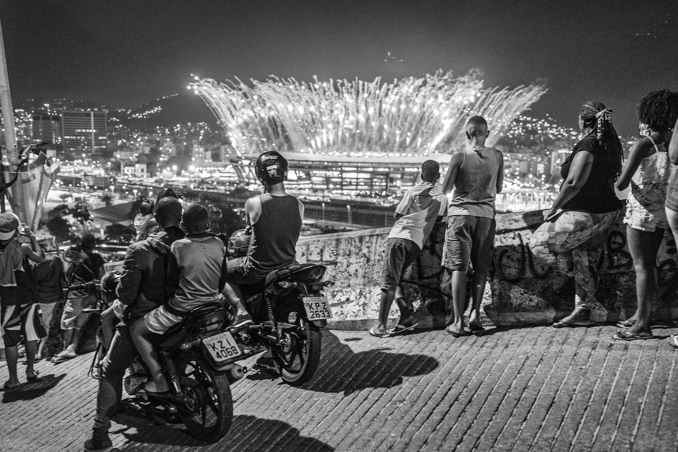 Residents of the Mangueira favela look at the fireworks during the opening ceremony of the summer Olympic games in the Maracanã stadium. Tickets to attend the opening ceremony inside the stadium reached a price of USD700. August 2016.