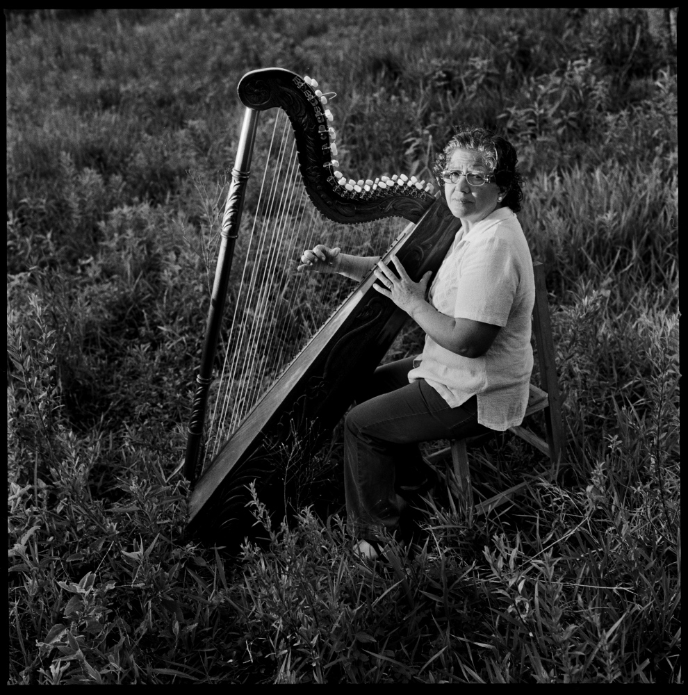 Celsa Ramirez, a former paraguayan political prisoner and a member of the Paraguayan Communist Party, playing the harp near her house in Ita, Paraguay.  Ms. Ramirez played the harp since she was a child, but during her years living underground as a member of the communist party she couldn't play for safety reasons. Only recently Ms. Ramirez came out of the traumatic experience during the underground years and the years she spent in jail, and started to play again.  Ita, Paraguay, November 2012.