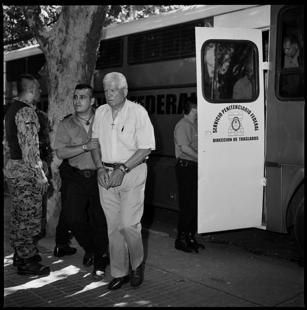Colonel Hugo Delme (white shirt) being transported from jail to the court house in Bahia Blanca by prision guards.   Mr. Delme is a retired army colonel accused of being involved in crimes against humanity by torturing and disappearing left-wing militants during the last Argentine dictatorship 1976-1983. He was convicted to life in jail in October 2012.  Bahia Blanca, Argentina, February 2012.