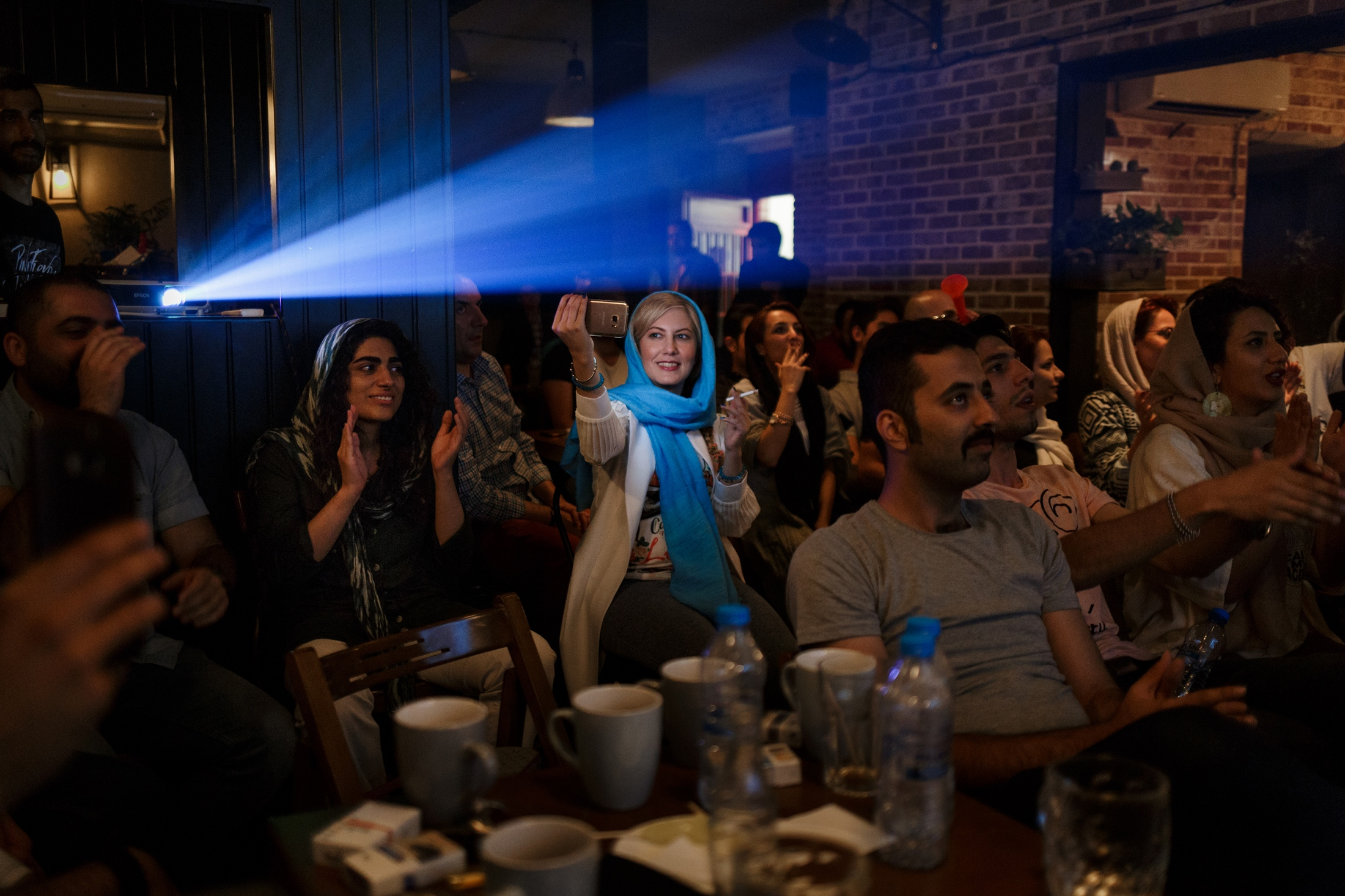 People watching Iran's world cup quali cation in a cafe in central Tehran. Women are not allowed to go to football stadiums in Iran. Some manage to get around this prohibition by dressing up as a man.