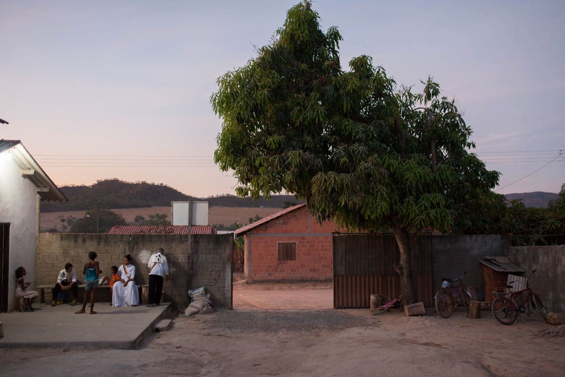 · Devotees hang out in the patio at dusk during a break. The temple is in a big lot which they have been fixing up for the past seventeen years. Cavalcante do Goais, 2015. //  · Devotos toman una pausa para un cafecito en el atardecer en el patio del templo. El templo se encuentra en un terreno grande y este ha estado en processo construcción durante los ultimos 17 años. Cavalcante do Goais, 2015.