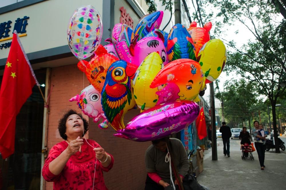 Señora comprando globos con imágenes de personajes de caricatura locales /Lady buying Chinese t.v character ballons. Xi'an