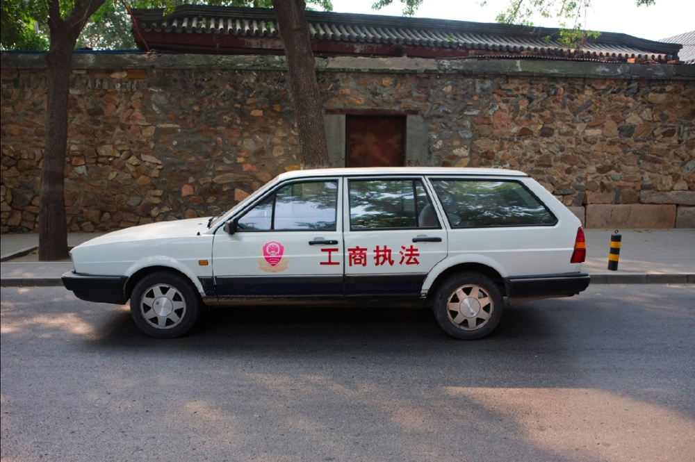 Coche de policía estacionado frente a una construcción antigua/ Police car in front of ancient building. Beijing / Pekín