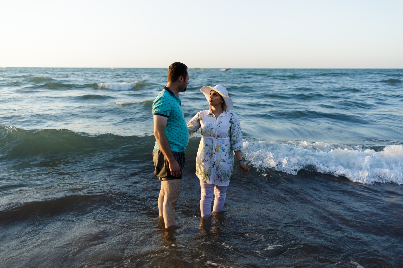 An iranian couple poses for a picture in the caspian sea.