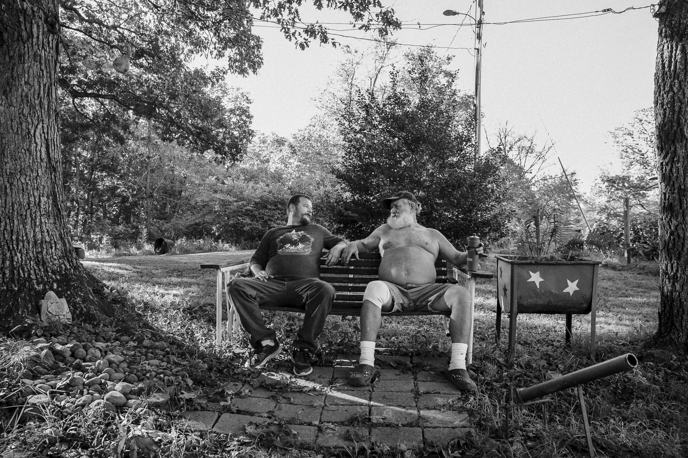 Anthony sits on a bench with his father Sam at his backyard. Even after Anthony's six months of sobriety, Sam said he was still afraid his son would relapse into meth addiction.