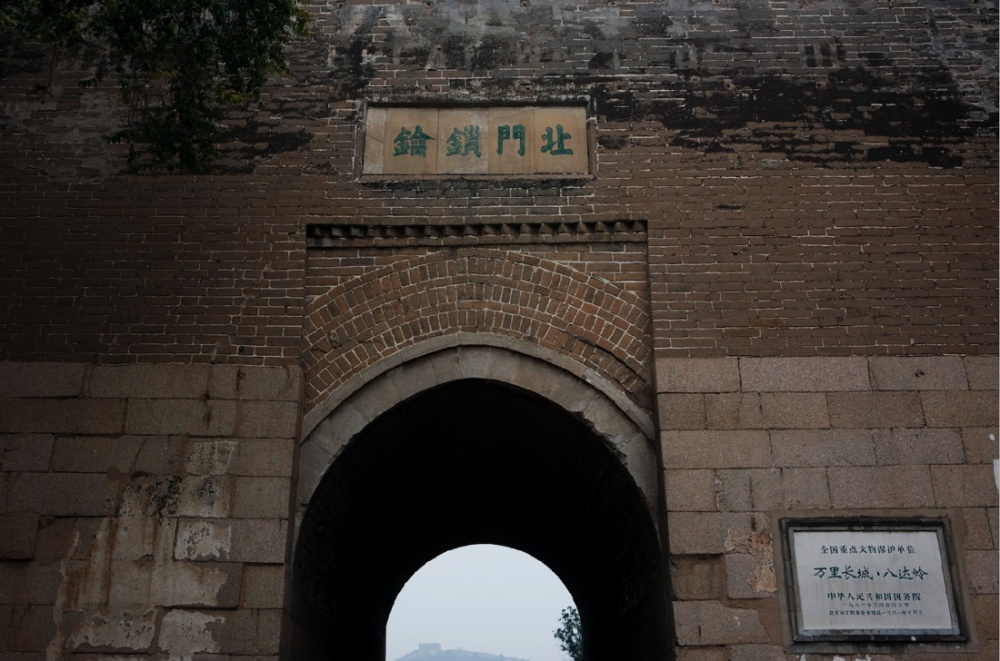 A la distancia, una de las cumbres de la Gran Muralla, vista desde el muro de entrada de una de las siete secciones abiertas al público / Great wall peak on the far distance at the entrance gate of one of the the seven visitable sections. Beijing / Pekín