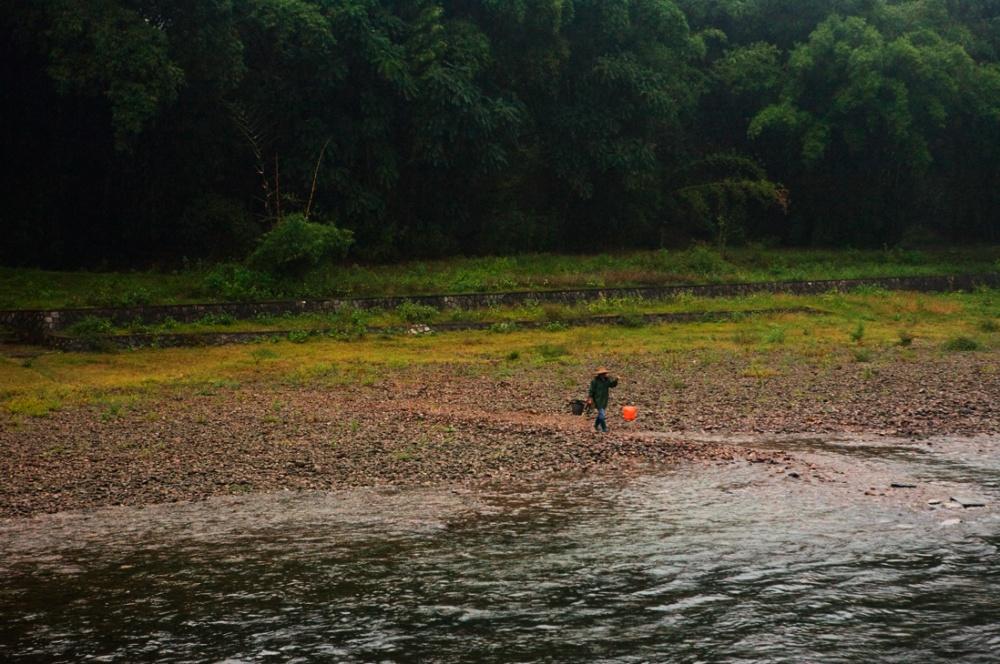 Habitantes de los poblados cercanos van a pescar en las orrilas del río / Inhabitants of local fishing villages seek the river as their source of water and food. Guilin