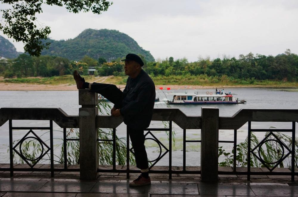 Un anciano haciendo ejercicio a la orilla del Río Li. Es muy común ver ancianos haciendo ejercicios en plazas y parques en diferentes ciudades de China/ An old man exercising at the edge of the Li River. It is very common to see seniors, in diferent cities, doing exercises in the morning and afternoons in parks. Guilin