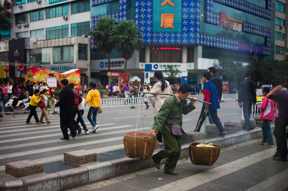 Comerciante cruzando la calle principal de la ciudad de Guilin, localizada en la provincia de Guangxi, al sur de China / Street seller crossing the main road in the city of Guilin, in the province of Guangxi, in the south of China. Guilin