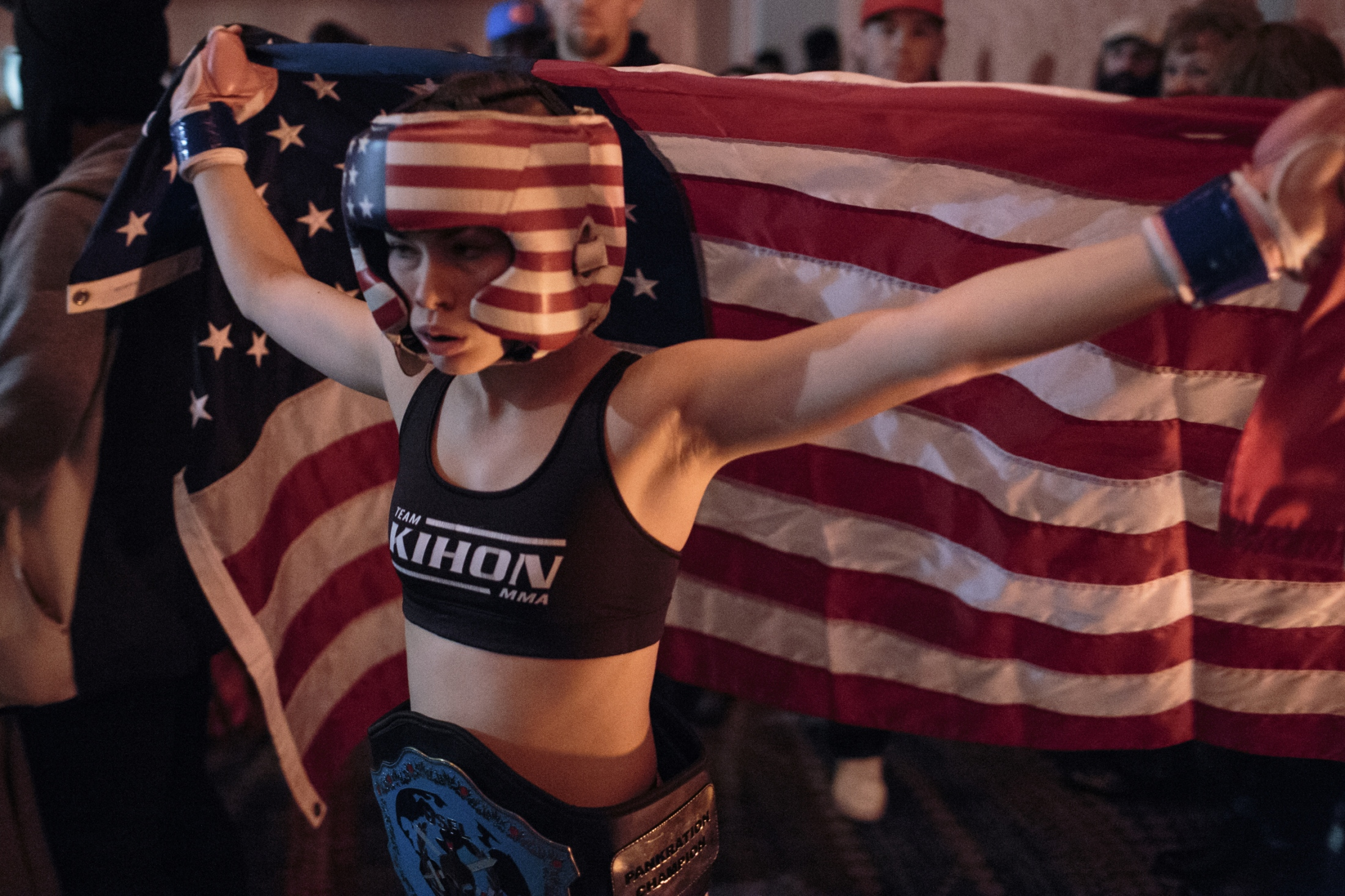Shaniyah Carlson, 15, carries the American flag to the cage before her 13th official Youth MMA fight during the U.S. Open Youth National.