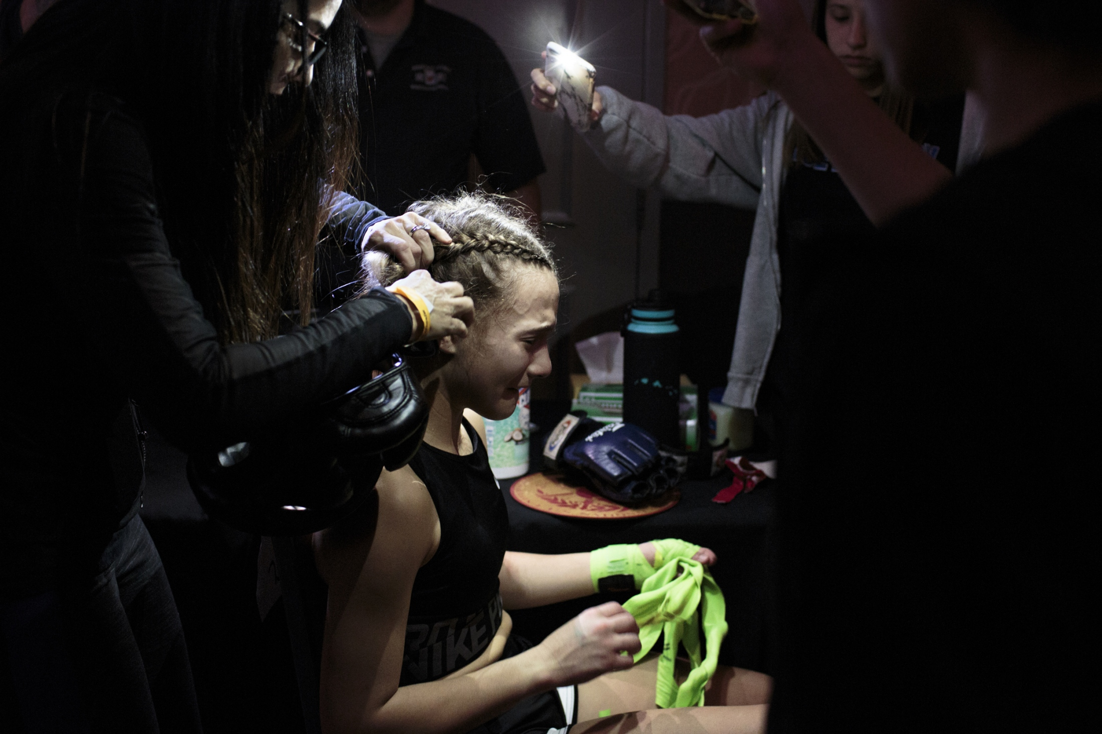 Family and friends help Teddy Mandala, 14, remove the tape and hand wraps after she lost her first official fight during the U.S. Open Youth National.
